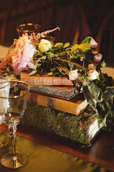 Pretty moss-covered books as centerpieces