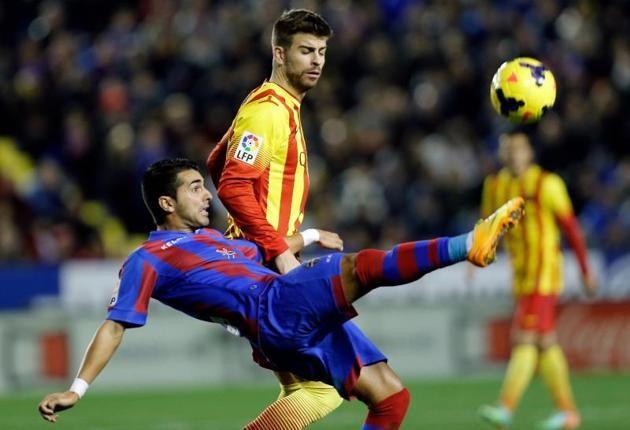 El delantero del Levante Ángel Rodríguez (i) y el defensa del FC Barcelona Gerard Piqué (d), durante el partido de la vigésima jornada de li...