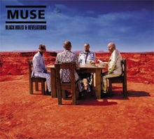 Black holes and revelations - Muse.The band sitting a a table outdoors, surrounded by barren land.