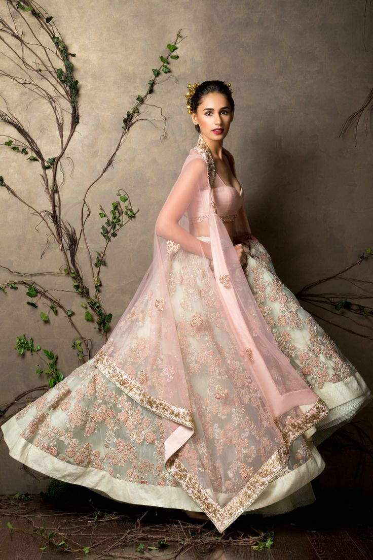 A peach pearl and dusty green high waisted raw silk and tulle lehenga with a lining of sparkles. The tone on tone embroidery has been done all over the lehenga. This is worn with a delicate work on dupatta. Sales@shyamalbhumika.com www.shyamalbhumika.com