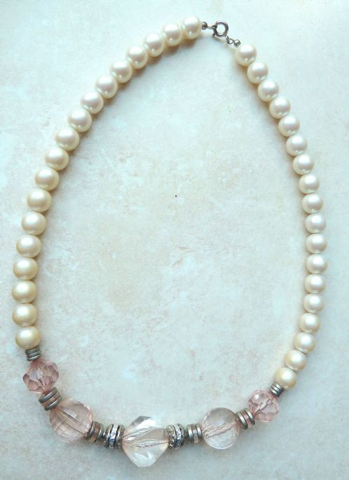 A stunning pearl  and clear Lucite faceted pastel pink bead necklace.  The necklace is fashioned from lovely large faux pearls, descending each side, moving into lovely large graduated in size, faceted,  transparent pink Lucite beads. These beads have silver tone metal  dividers, four with central pink Lucite detailing. The necklace has a spring ring fastening.  A stunning vintage statement necklace. Circa 1960's.
