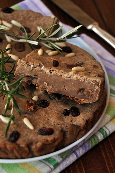 Italian food - Castagnaccio  Ingredients:  - 300 gr. chestnut flour  - 20 gr. granulated sugar  - 20 gr. brown sugar  - 4 tablespoons of extra virgin olive oil  - A pinch of salt  - 40 gr. raisins  - 40 gr. pine nuts  - Water as required for a fluid mixture without lumps  - Sprigs of rosemary (optional)