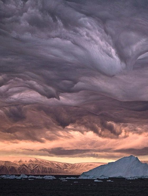 """""""Stratus Clouds, Greenland"""" - Eight hundred miles south of the North Pole, stalactite-like stratus clouds—churned by 90-mile-an-hour winds—and the light of a bruised dawn paint an apocalyptic portrait over Inglefield Bay."""