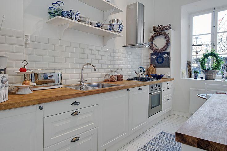 LA COCINA IDEAL. Es espaciosa, luminosa, con muebles blancos, encimera de madera, espacio de almacenaje, azulejos Metro, preciosos adornos y detalles y un coqueto rincón para comer.