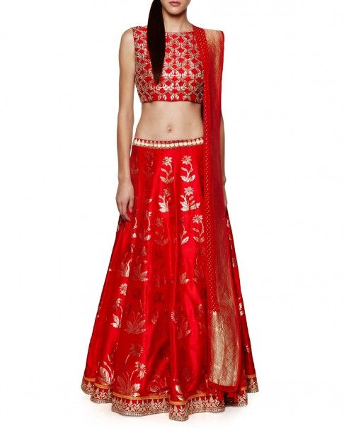Anita Dongre - Scarlet lengha with floral hand woven designs. Gota patti work adorn the hemline and waist. This set comes with a matching sleeveless blouse featuring gota patti work and sequins. Boat neckline.
