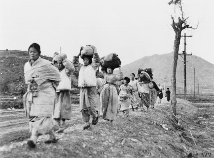 Korean refugees leaving the battle area - women and children carrying their belongings walking along the side of the road. There are no men in the group, as they had all been conscripted. © IWM (BF 397)