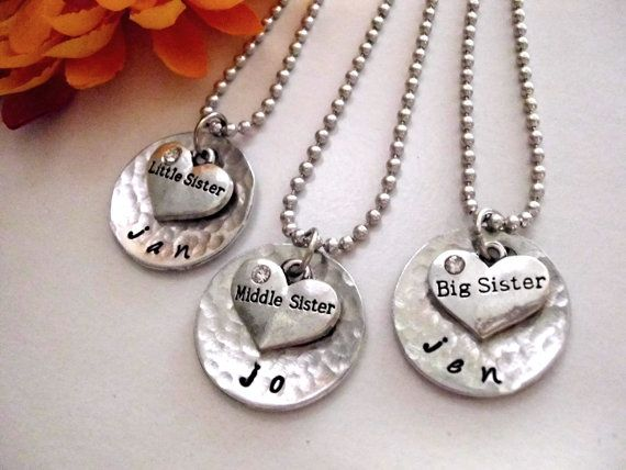 Please allow 10 days or so for production time, plus shipping time. Please read all shop policies BEFORE ordering. Check avatar caption for real time updates. This three sister necklace set comes with little sister, middle sister, and big sister rhinestone heart charms (I cannot alter the heart charms) each with a personalized hand stamped name on a hammered aluminum disc. Cute! Comes on a 24 aluminum ball chain. I have a number of other sister jewelry sets in my shop. Each is available…