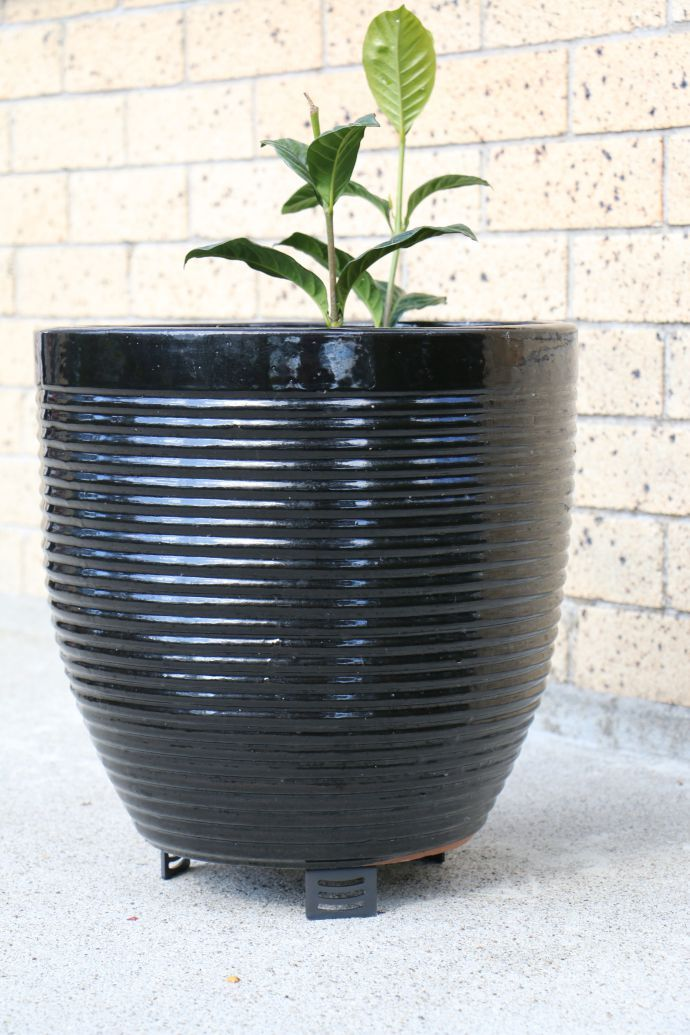 Pot Plant Stand - Black anodised showing how the plant pot is kept off the concrete.  Easy to hose clean underneat without trapping water and soil that results in staining.