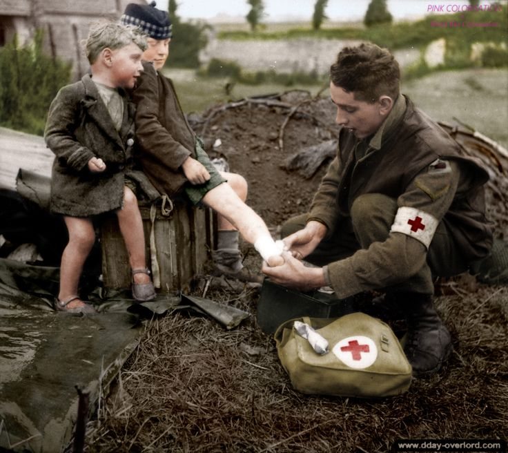 The Canadian Medic First Class J.W. Curtis bandages the burnt leg of a French…