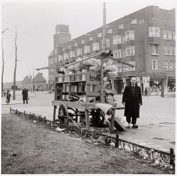 1950's. Flower vendor at the Scheldestraat in Amsterdam-Zuid. In the background a store of the grocery store chain De Gruyter. #amsterdam #1950 #Scheldestraat