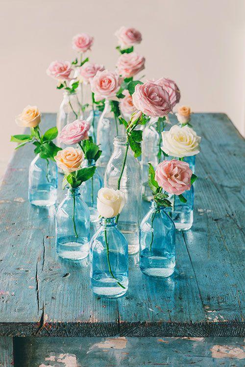 Single stems in blue glass bottles for your something blue wedding decor!
