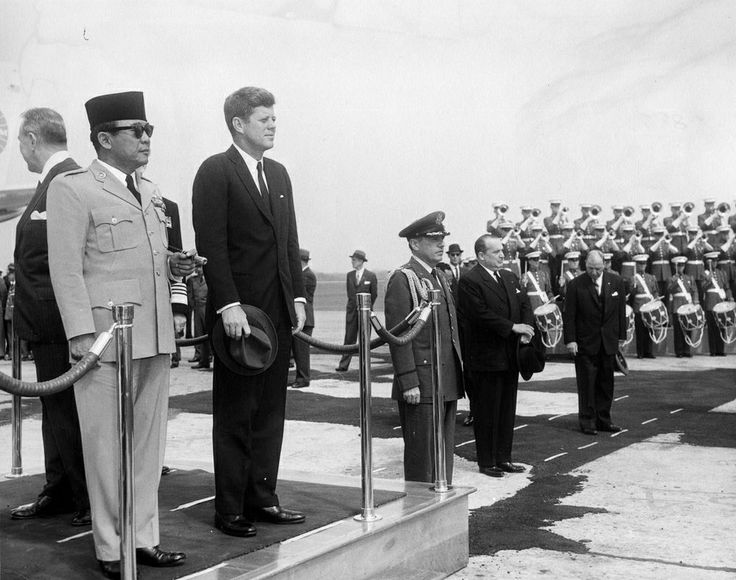 1961. 24 Avril. By Abbie ROWE. President John F. Kennedy stands with President of Indonesia Ahmed Sukarno at Andrews Air Force Base, Suitland, Maryland. Under Secretary of State Chester Bowles stands behind President Sukarno; Air Force Aide to the President Godfrey T. McHugh stands right of the President off stage. The United States Marine Corp Band plays in background