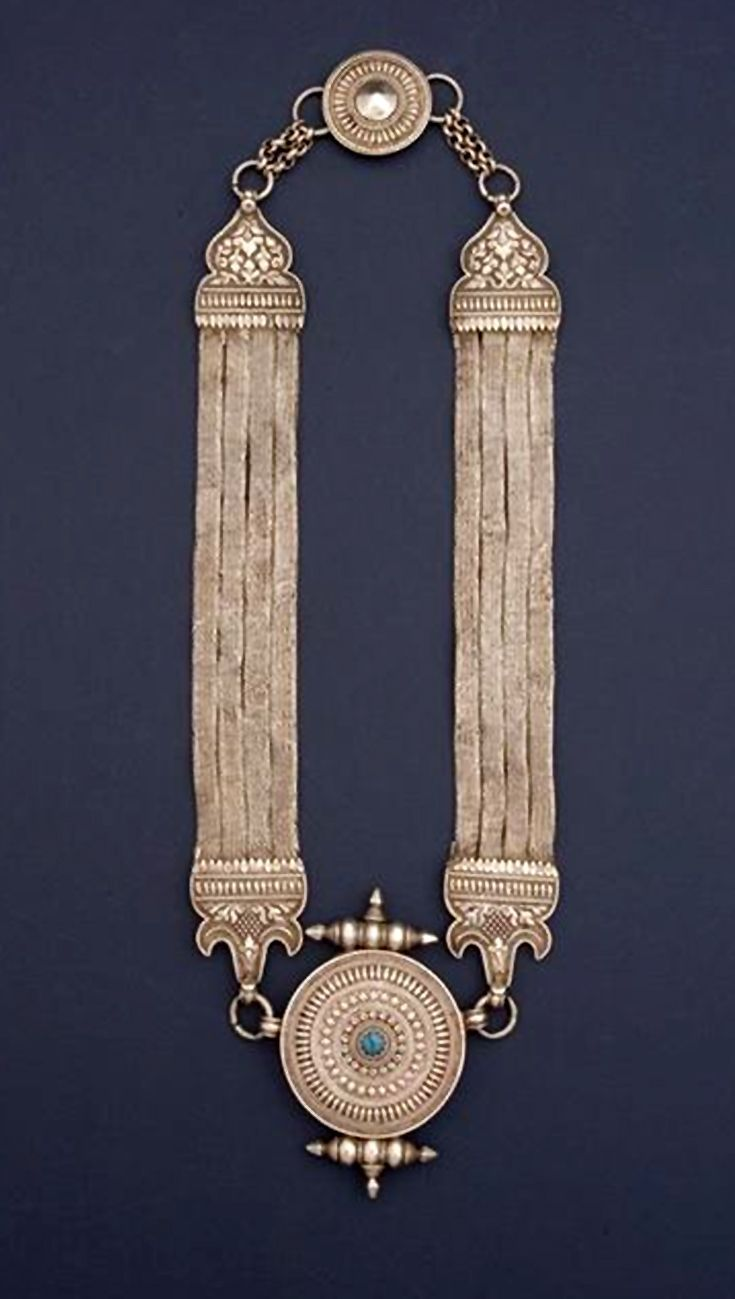Amulet necklace decorated with lotus flowers (stylised in the clasp at the top and the circular amulet box at the bottom) and thunderbolts (one on each side of the amulet box). The motifs at the ends of the supporting bands are vegetative designs. Made of high quality silver and a turquoise. This type of necklace used to be popular in East Nepal.
