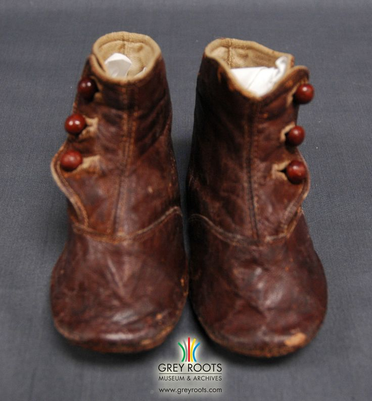 A pair of brown leather, button-up, child's boots with a canvas interiors. The boots have three buttons on the outside. Grey Roots Museum & Archives Collection.