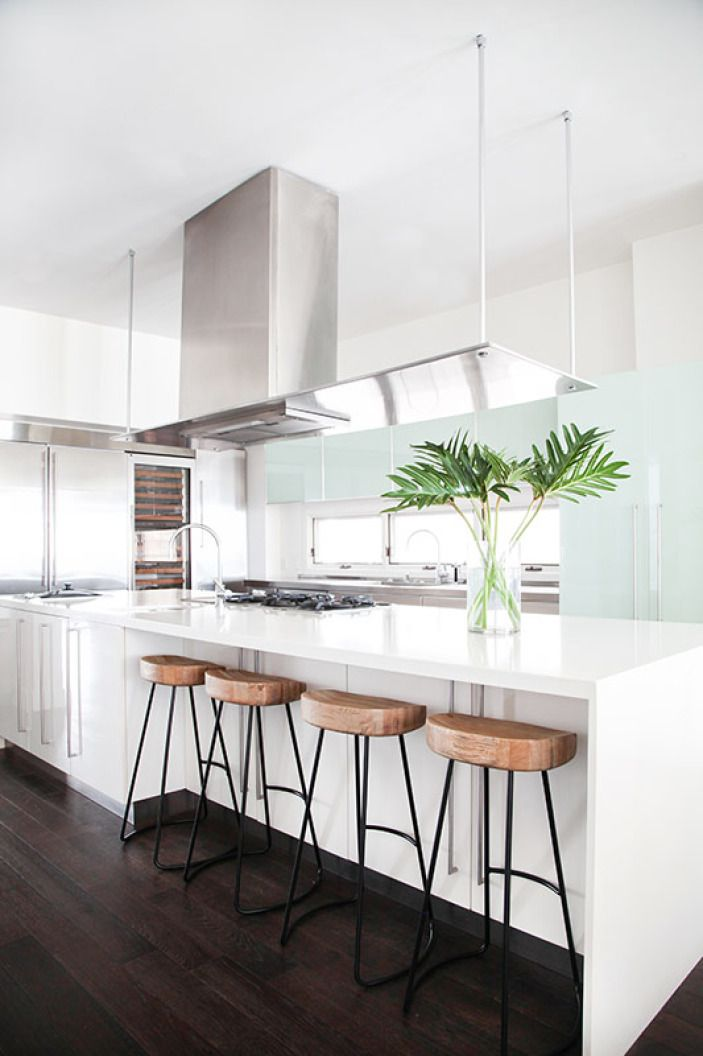 The ultimate, contemporary kitchen, this space is actually inside a West Coast beach house. The minty glass cabinetry and wooden stools keep the room from feeling too sterile and extended range hood dissect the space and separates it from the open living and dining areas.