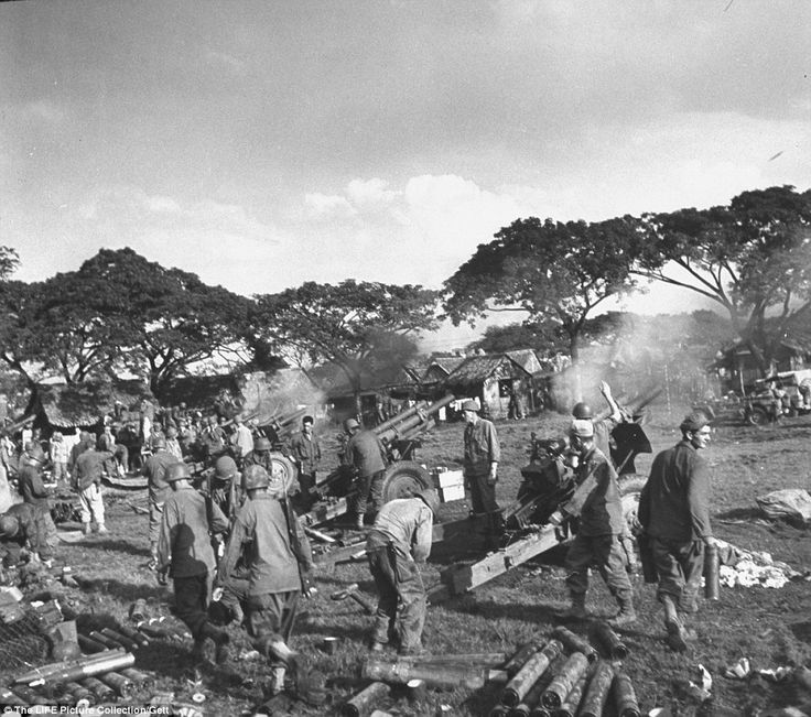 War: American artillery crews firing on Japanese positions from the grounds of the recently liberated Santo Tomas University during the Battle for Manila. ended the three-year Japanese military occupation in the Philippines