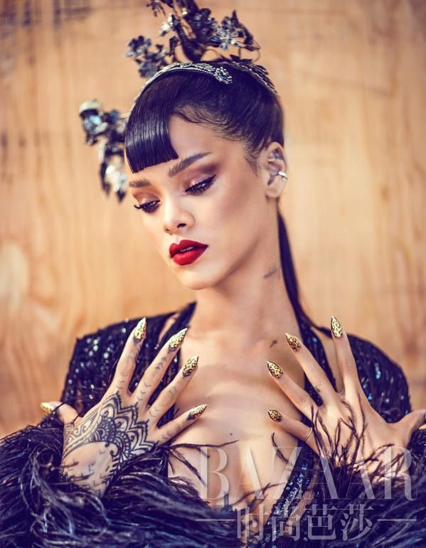 Showing off a golden manicure and red lips, Rihanna nails the beauty look as well as fashion.