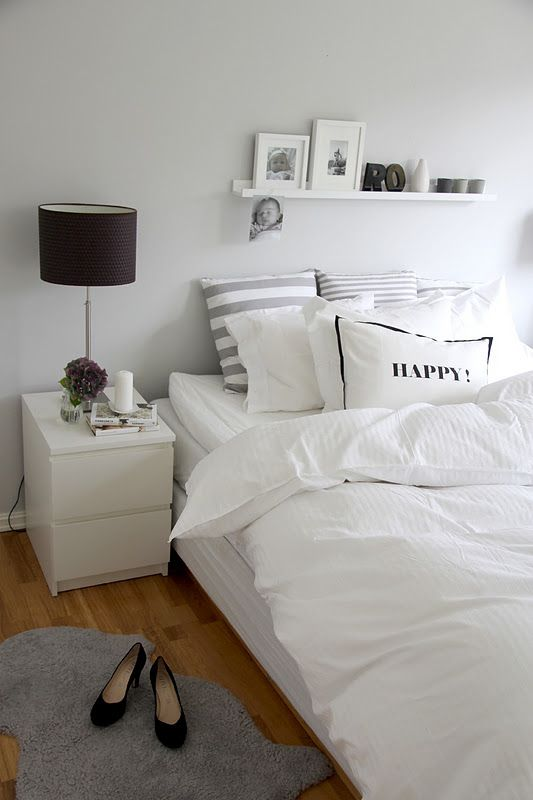 Striped pillows, fluffy comforter, gray sheepskin rug. <3