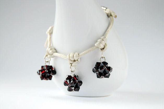 Satin cord bracelet - bransoletka wykonana z satyny w kolorze kości słoniowej i ozdobiona trzema kulkami wykonanymi z kryształków SWAROVSKIEGO - BICONE - GARNET (ciemna czerwień). Dodatkową ozdobę stanowią japońskie...
