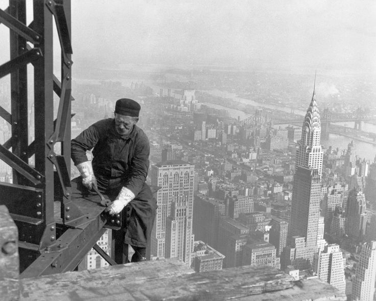 Worker on the Empire State building with the Chrysler building in the background.
