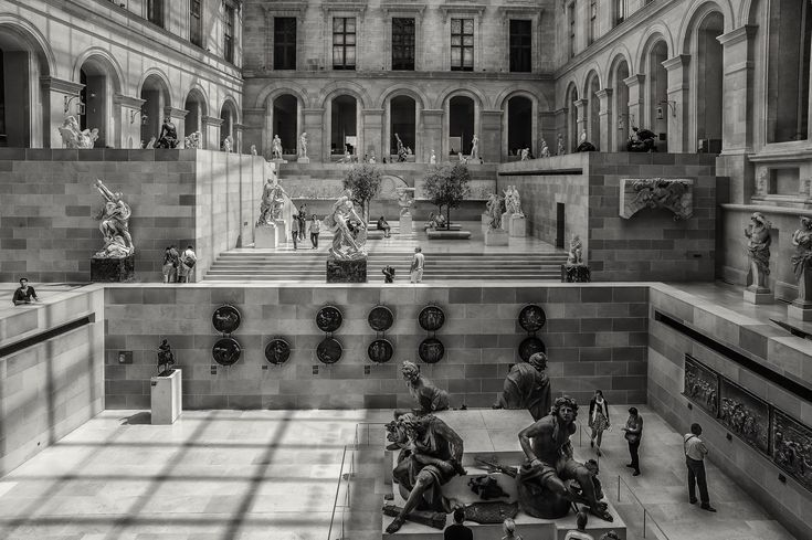 Visitors exploring an amazing space within the Louvre museum in Paris, France. This image explores light, tone and shape to help tell the story.