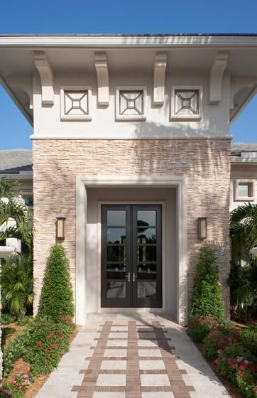 Florida home with stucco and stacked stone accents, stone walkway, square geometric pattern on stone walkway