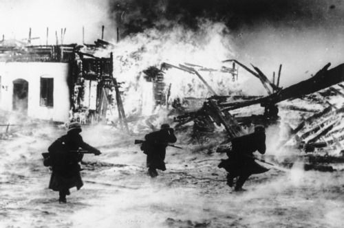 German soldiers flee a burning Norwegian village during the spring of 1940.