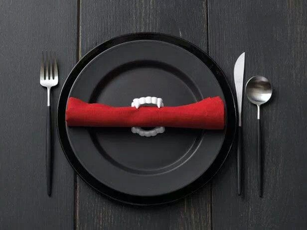 I AM DEFINITELY DOING THIS FOR MY DINNING ROOM TABLE!  Haha!  I love it!  Plastic vampire fangs as napkin rings.