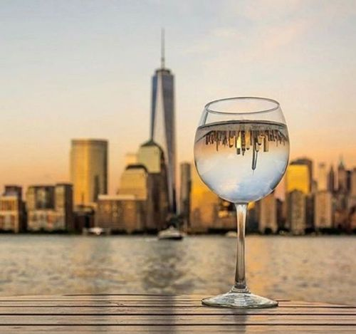 NYC. The colors of the sunset reflected in a glass of white wine.  winegram.it share your wine