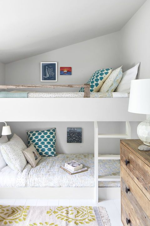 Built-in bunk beds in the daughters' shared room reinforce the home's understated rustic vibe. The simple, streamlined bunks and ladder, for example, balance the reclaimed driftwood railing and dresser made from old barnwood.