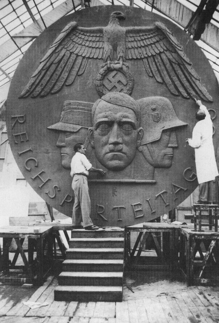 Artists work on a large insignia for the Reichsparteitag, which depicts the Sturmabteilung, Hitler, and the Army under the downswept wings of the Nazi eagle.