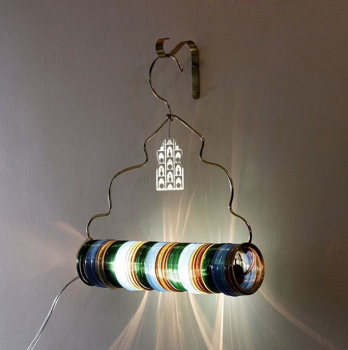 Choori in Hindi means Glass Bangle. This lamp is inspired from Indian women using clothes hanger for hanging their glass bangles. A light that creates atmospheres with colors and shadows. The colors appeal to mood and the soft clinging sound to senses. It can be used as a single unit or can be an ensemble of many creating an installation of colored lights. It's an evening light for parties, social gatherings and also for solitude.