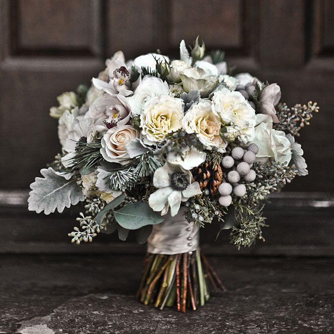 Winter wedding bouquet of mini cymbidium orchids, silver brunia, juniper, pine boughs, anemones, pine cones, garden spray roses, seeded eucalyptus, Vendela roses, and dusty miller