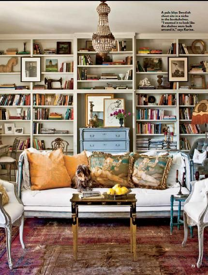 Wonderful bookcase wall, chandelier, sofa and pillows. Wonderful Swedish sofa and chairs. Note all the art and mirrors on the bookcases.