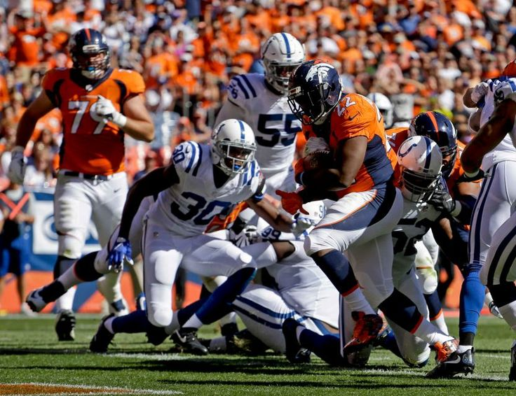 Denver Broncos running back C.J. Anderson (22) scores against the Indianapolis Colts during the first half of an NFL football game, Sunday, Sept. 18, 2016, in Denver.