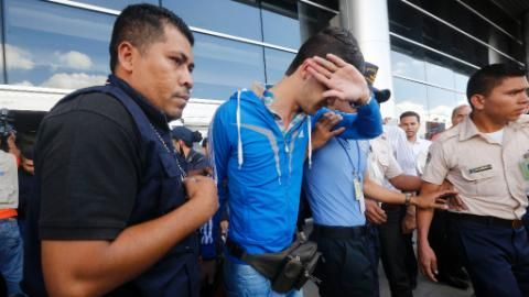 Honduran policemen escort one of five Syrian citizens arrested at the Tocontin international airport in Tegucigalpa on November 18, 2015 with stolen passport from Greece. All five Syrians were heading to the U.S
