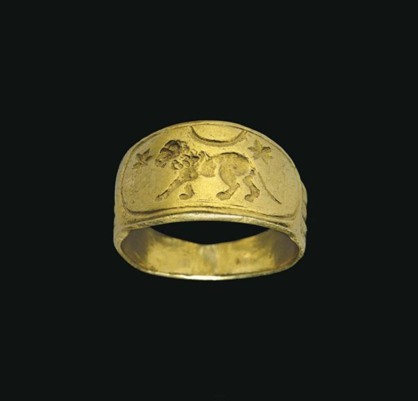 A ROMAN GOLD FINGER RING CIRCA 2ND CENTURY A.D. Solid cast with a wide flat hoop, ridged on the exterior, the ridges rising up in three flutes on the shoulders, the elongated oval bezel engraved with a lion walking to the left, a crescent moon and two stars above, the device encircled by a line border
