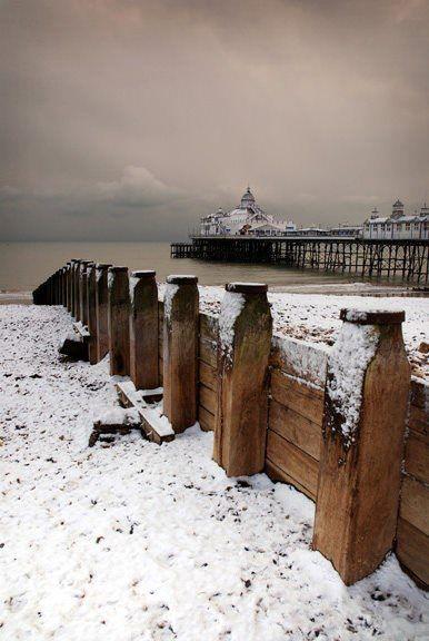 Eastbourne Pier and beach winter snow scene.