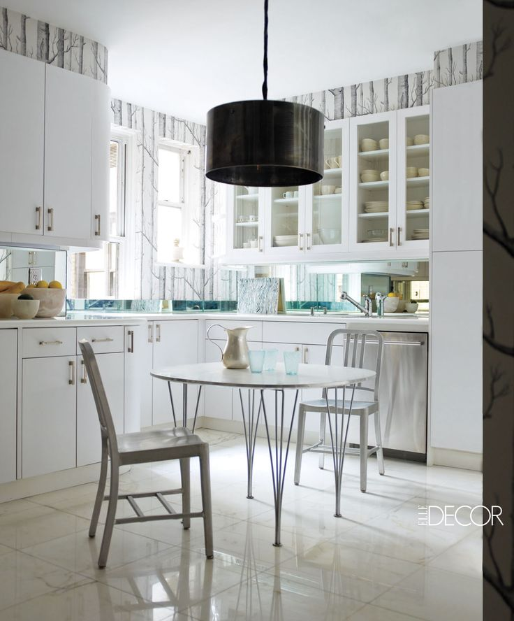 In the kitchen,  a vintage industrial light fixture  is suspended above a 1960s table surrounded by Emeco chairs; the cabinetry hardware is by Restoration Hardware, the dishwasher is by LG, the wallpaper is by Cole & Son, and the floor is of Calacatta marble.   - ELLEDecor.com