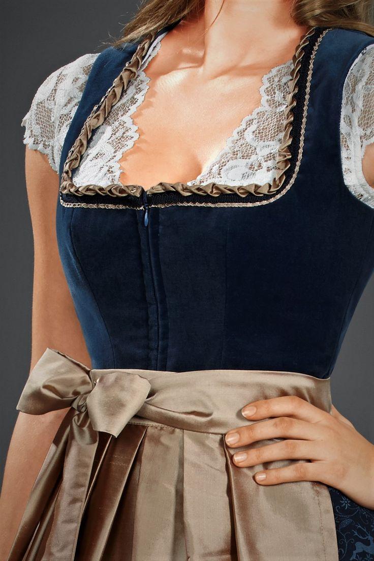 Das AlpenHerz Dirndl Elisabeth überzeugt durch seine Schlichtheit und Eleganz. Das Mieder aus hochwertigem Baumwollsamt in blau mit goldener Borte ist edel und schlicht zugleich.