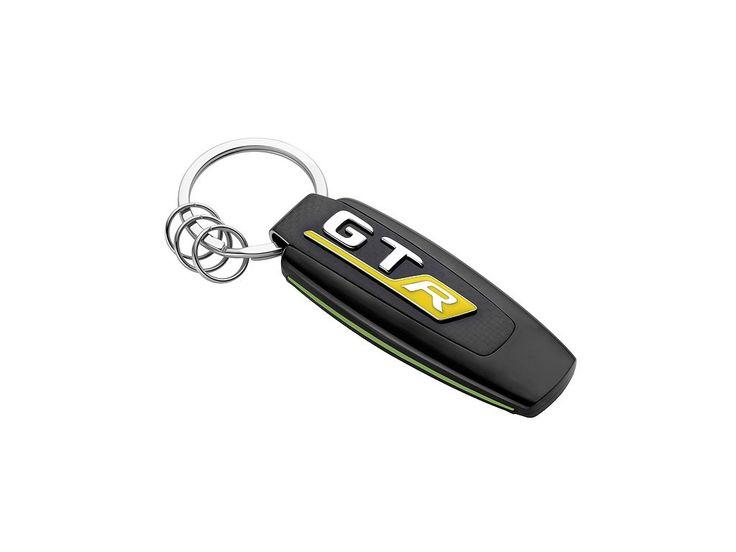 Přívěšek - klíčenka AMG GT R. Stříbrná -černá - zená. Nerezová ocel -carbon. Plochý dělený kroužek s třemi dalšími mini-dělenými kroužky pro rychlou výměnu -odstranění jednotlivých klíčů. Logo AMG na přední straně. Navrženo v Německu. Délka cca 9 cm.