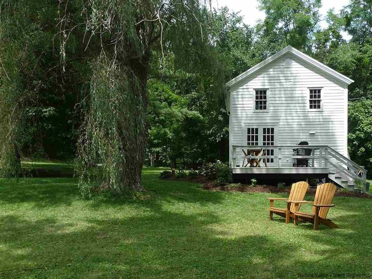 Side exterior of charming white country house with deck and Adirondack chairs. (Click through for full house tour.)