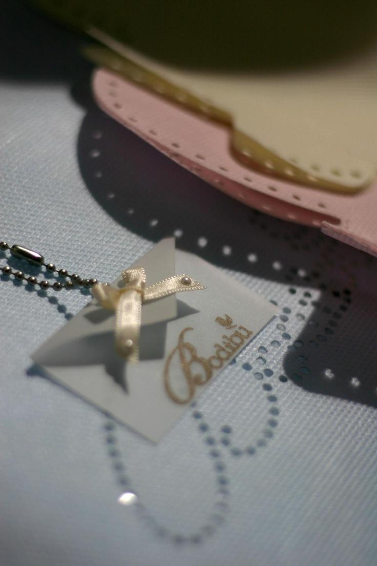 Dettagli Bodibù:cartellino in carta pergamena con fiocchetto di raso e perline