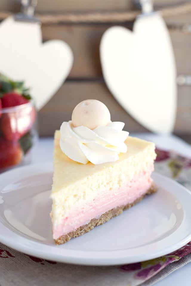 a slice of strawberries and cream cheesecake sitting on a plate with a floral na…