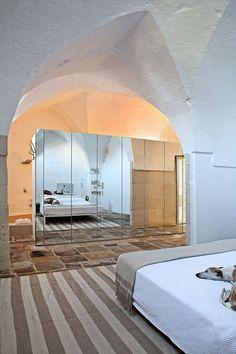 Il moderno sposa l'antico in questa camera da letto. Armadio con ante a specchio. Dietro l'armadio la vasca da bagno.