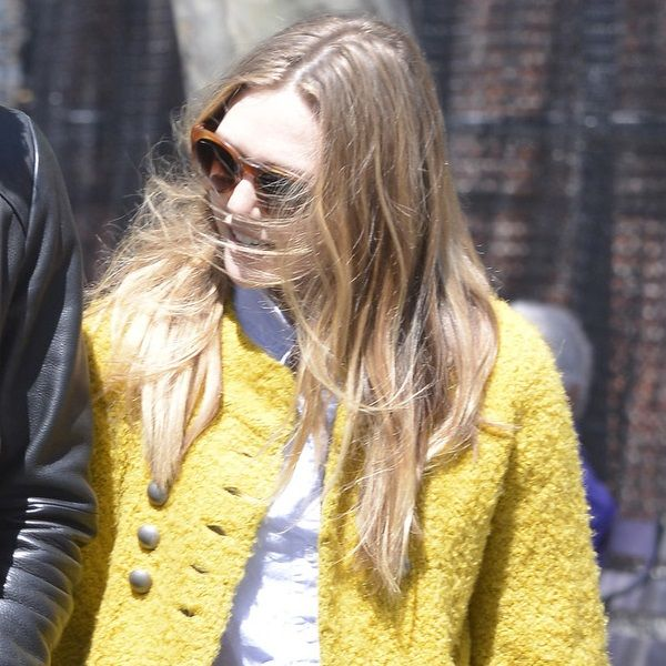 Elizabeth Olsen wearing a yellow coat over a white top