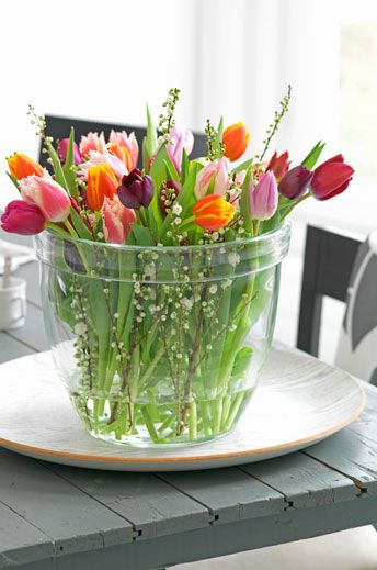 Mooie mix van gekleurde tulpen in een glazen vaas op een ronde witte schaal