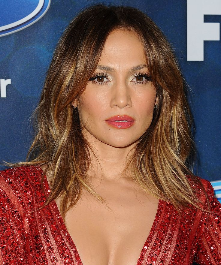 Jennifer Lopez turns heads at the American Idol finalists party in a plunging sparkling red catsuit.