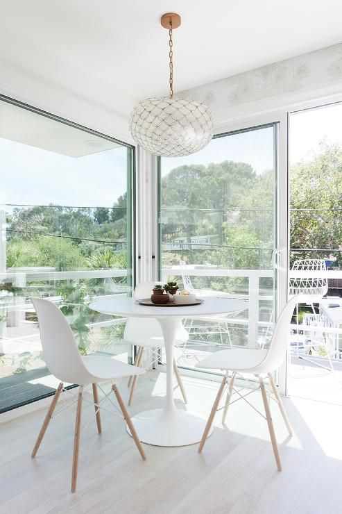 Sun filled breakfast room features an Ikea Docksta Table lined with Eames Molded Plastics Chairs illuminated by a Serena & Lily Capiz Scalloped Chandelier surrounded by sliding glass doors which lead out to the deck.