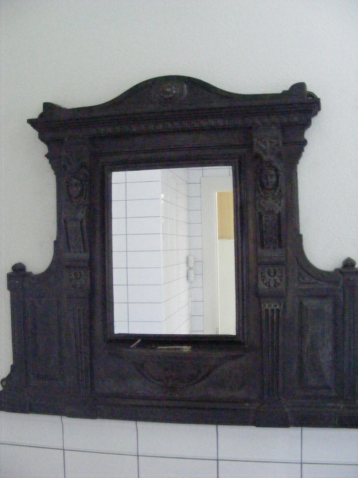 Vintage Victorian Iron Bathroom mirror.  It would have originally have been a mantelpiece mirror.  I spent a long long time stripping it of it's original purple paint and cleaning it up. It weighs a lot but it is the perfect centrepiece to my bathroom/laundry under the stairs in the original 120 year old part of the house. If you look closely you can see two faces in the ironwork.